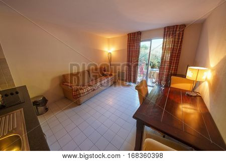 SAINT-TROPEZ, FRANCE - AUG 2, 2016: Interior of hotel room, view of kitchen and living room with television set and French window, girl (with model release) sitting on terrace