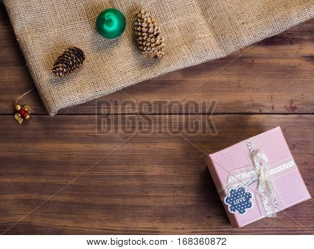 Vintage gift box, fir cones, Christmas toy, ribbon with bow on wood and burlap vintage background, photo top view. Copy space for text. Top view, Studio photography