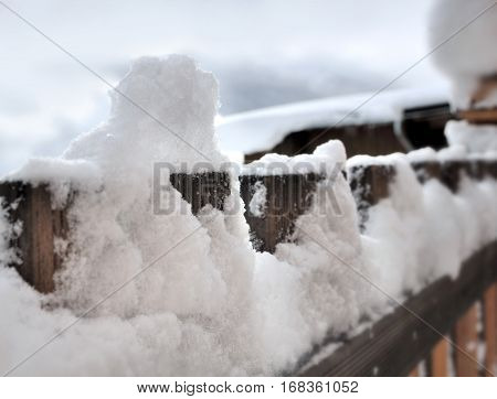 close on a pile of snow on wooden railing of a balcony