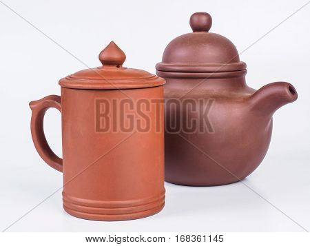 Picture of the brown infuser teapot near light brown tea cup. Infuser teapot and tea cup on white background. Handmade earthenware. Side view.