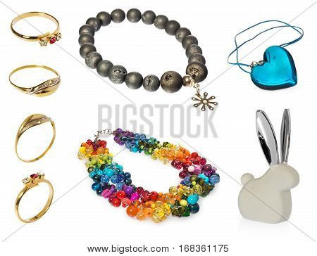 composition of jewelry: - Blue crystal heart pendant - Bunny ears with silver - Necklace with olive beads - Necklace with colored crystals and beads - Gold rings engraved, diamonds and ruby Objects on white background with light shadow and reflection.