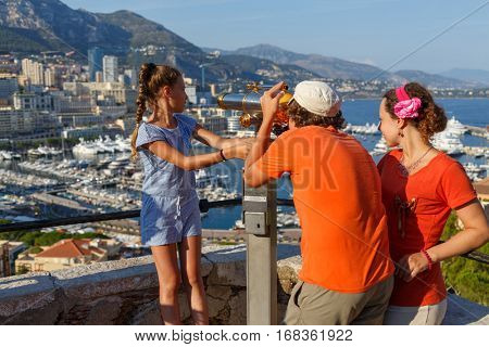 mother with two children on observation deck of palace Grimaldi, boy looks through binoculars