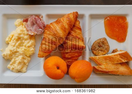millet porridge, ham, croissants, peaches, bread, jam and figs at compartmental dish