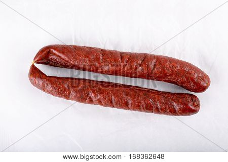 Smoked salami sausage on white. Copy space.