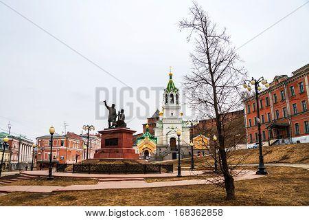 Nizhny Novgorod, Russia. Minin and Pozharsky monument near Kremlin during the cloudy day in Nizhny Novgorod, Russia. Trees and historical buildings
