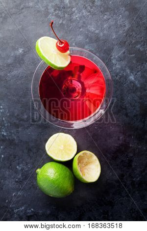 Cosmopolitan cocktail on dark stone table. Top view
