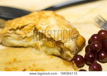 A shot of freshly baked brie cheese with orange marmolade with grapes next to it.