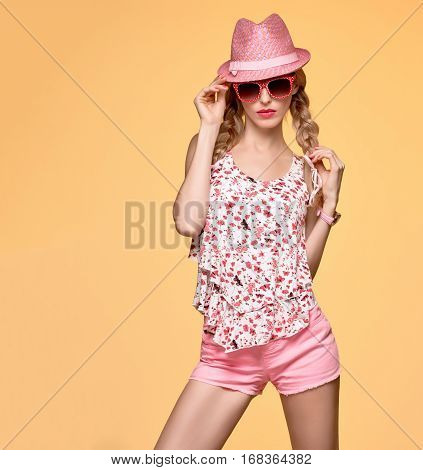 Fashion Hipster woman in Stylish Spring Summer Outfit. Cheeky emotion. Sexy Blond Model Crazy Girl, Fashion Sunglasses, Glamour Pink Shorts, Floral spring Top.Trendy pink fashion Hat.Summer Hairstyle