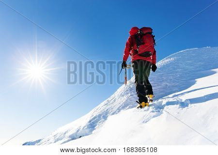Extreme winter sports: climber reachs the top of a snowy peak in the Alps. Concepts: determination, success, brave.
