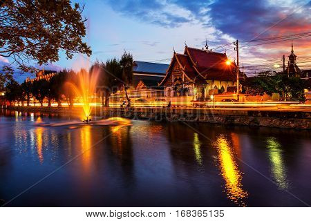 Chiang Mai, Thailand at sunset. Lively street in popular touristic town Chiang Mai, Thailand. With illuminated historical buildings and water reflection.