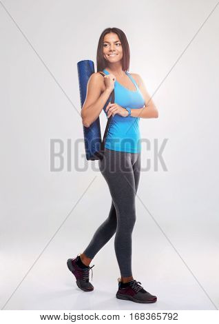 Full length portrait of a smiling sports woman with yoga mat walking over gray background. Looking away