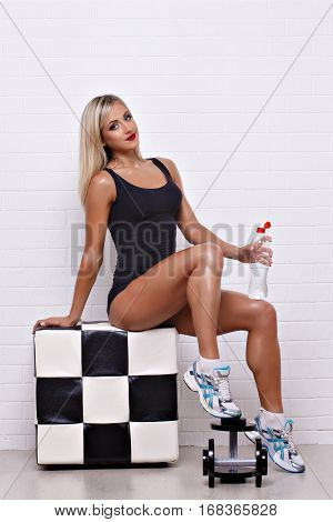 Portrait of attractive blonde woman in bodysuit sitting on chekered poof with bottle of water and dumbbells