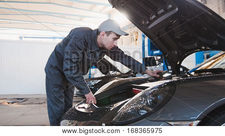 Hood for the sportcar - mechanic in automobile garage, telephoto