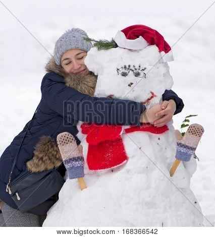 winter theme - girl hugging a snowman outdoors