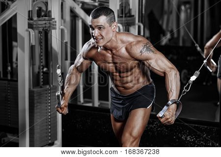 Athlete Muscular Bodybuilder Man In The Gym Training With Simulator