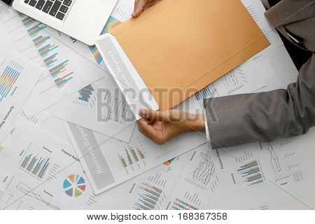 Businessman Open Brown Envelope For Evaluating Business Report, Examining Report Papers On Table In