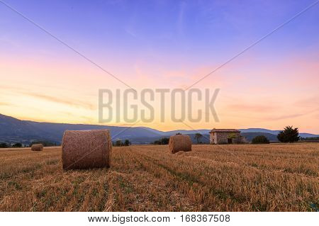 Sunset Over Farm Field With Hay Bales Near Sault
