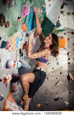 Young sporty woman bouldering in climbing gym