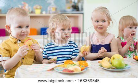 funny kids eating fruits in kindergarten dinning room