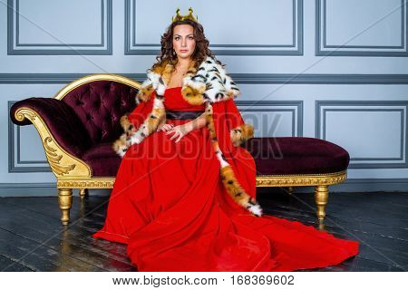 Woman in red dress, cloak and with crown on head sits on couch in room.