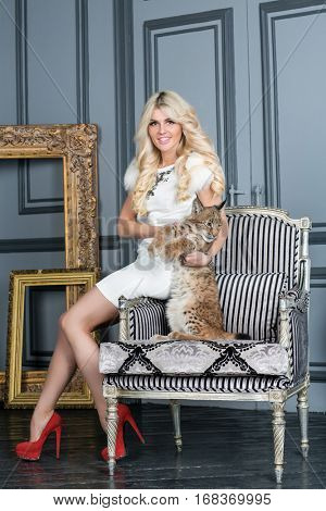Young blonde woman sits on armrest of armchair with lynx cub.