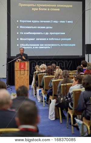 MOSCOW, RUSSIA - NOV 13, 2015: People in congress park of Radisson Royal Ukraine hotel during international congress Manage Pain. Principles on use of opioids for pain in back inscription at screen.