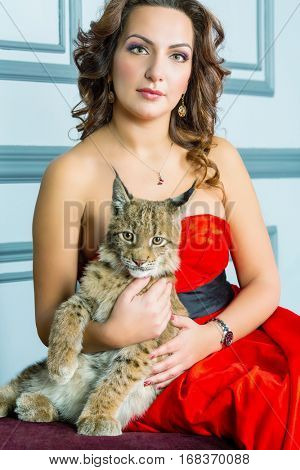 Woman in red dress sits on couch holding lynx cub.