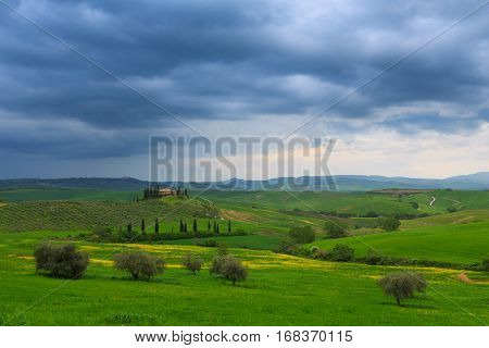 Tuscany landscape at dramatic sky. Typical for the region tuscan farm house hillsItaly