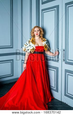 Blonde woman in red dress and fur mantle stands holding on door handle.