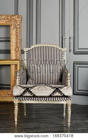 Silvery armchair and golden frames in room with grey walls and black floor.