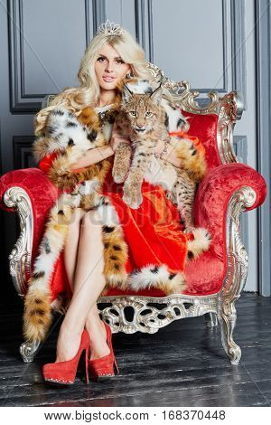 Young blonde woman in red cloak and crown sits in armchair playing with lynx cub.