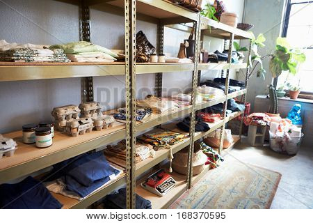 Clothes and ephemera displayed on shelves in a clothing shop