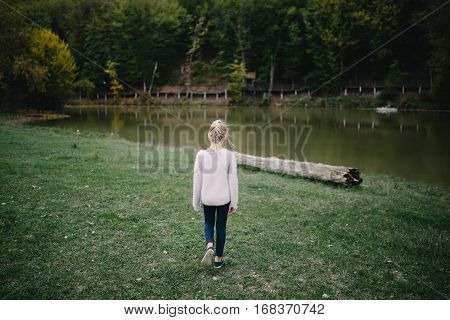 sad little girl goes alone on the shore of the lake. back view