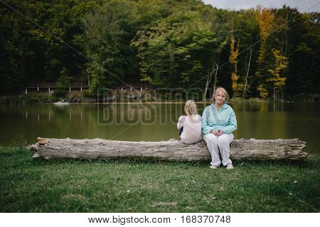 little girl turned her back on the senior woman. offended girl and an elderly woman sitting on a log in the background of the lake. conflict of generations. family problems.