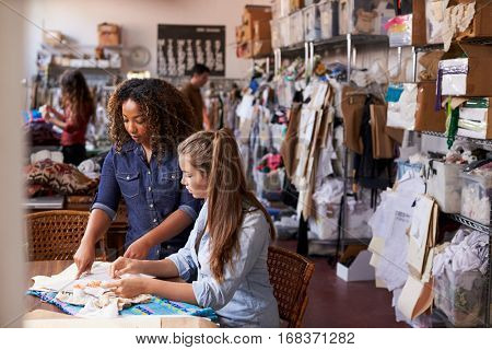 Woman stands to train an apprentice at clothes design studio
