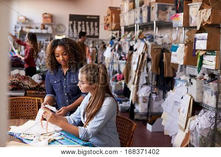 Woman training apprentice at clothes manufacturing workshop