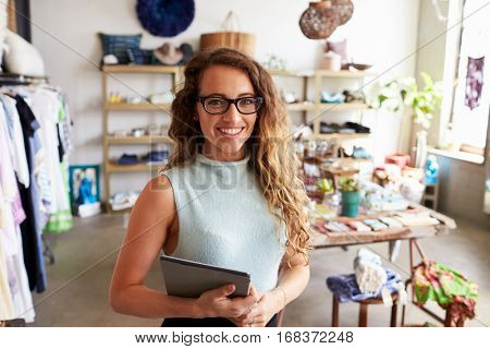 Female business owner holding tablet computer in clothes shop