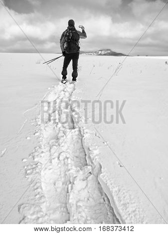 Man With Snowshoes And Backpack Take Photos By Smartphone. Hiker In Snowdrift