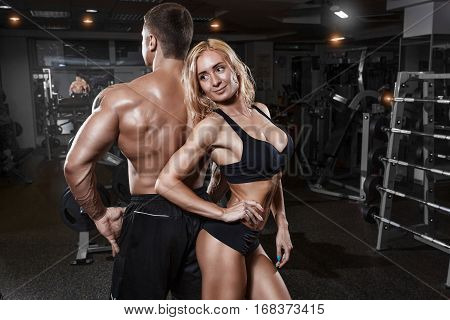 Young sporty beautiful sexy couple show muscules in gym