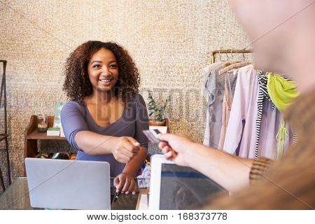 Assistant at clothes shop taking credit card from customer