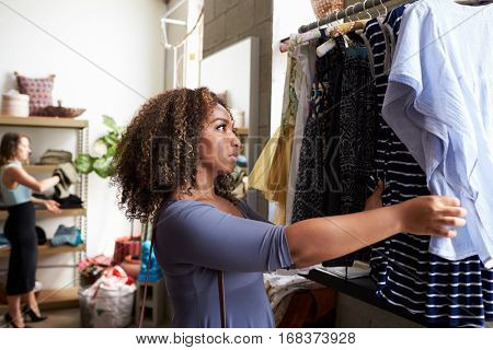 Customer looking at clothes on a hanging rail in a boutique
