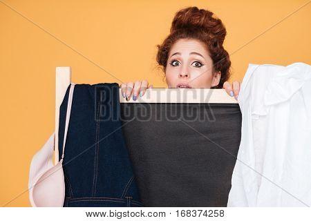 Cute young woman standing behind folding screen