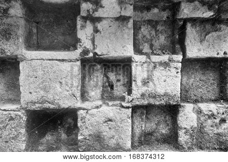 background and the abstract textured surface of an ancient stone wall of monochrome tone