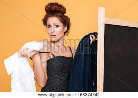 Confused cute young woman choosing clothes behinf golding screen
