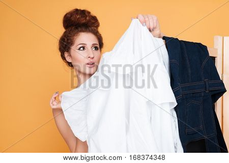 Charming young woman standing and choosing clothes behind folding screen