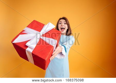 Happy excited young woman giving you gift box over yellow background