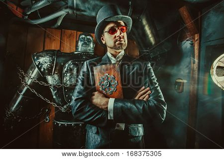 Young Bearded Man In Cylinder Hat Is Reading Manual Book While Standing Near Huge Robot.