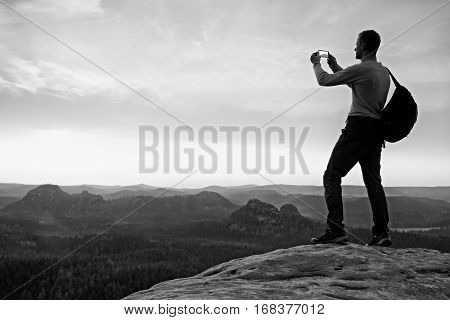 Tall Backpacker With Phone In Hand. Spring Daybreak In Mountains.