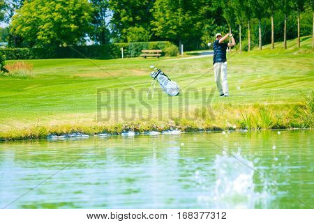 golf player hitting the ball into a lake