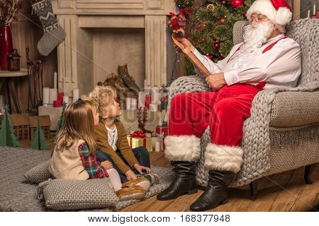 Santa Claus reading wishlist and children looking at him